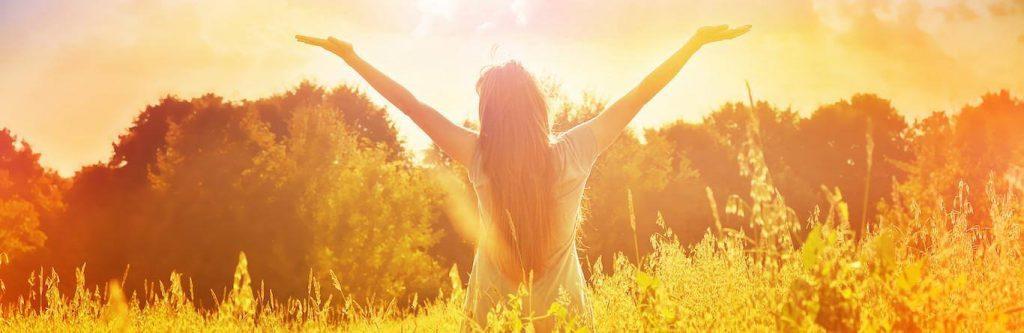 woman stands facing backward raising hands gratitude life in field in sunny sky