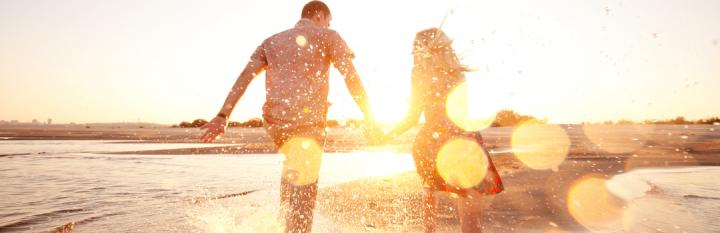 couple holds hands walking along beach in beautiful sunny sky