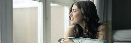 young woman sits beside window smiling hugging white pillow