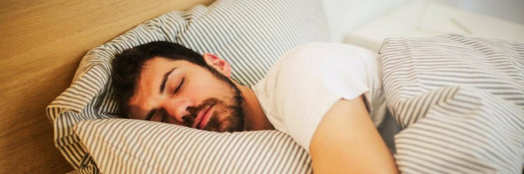 man sleeps tightly on bed covering body with stripped blanket