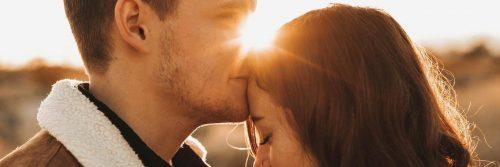 man kissing girlfriend forehead in sunny sky