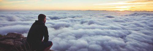 man sits on rock watching clouds beautiful sunset