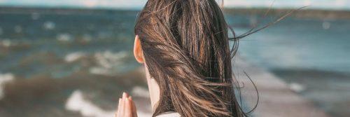 woman facing backward looks at ocean
