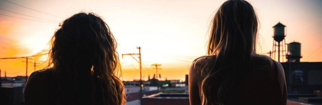 two women stands facing backward looking at inner city street sunset sky