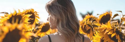 woman facing backward walks between sunflower garden in sunny sky