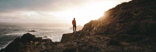 man stands hands in pocket on rock beside ocean looking at sunny sky