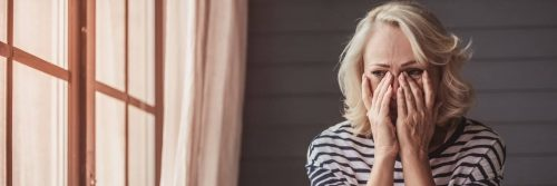 woman hands on face crying worrying feeling hurt sitting beside window