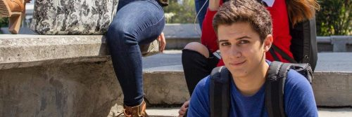young man sits on stairs smiling in university campus
