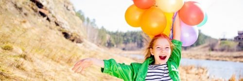 girl stands on field beside lake holding balloons happily smiling