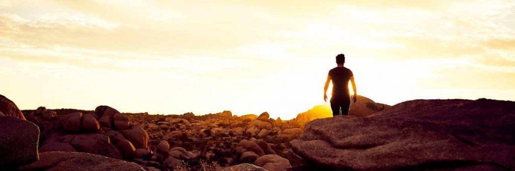 man walking between rocks in sunny sky