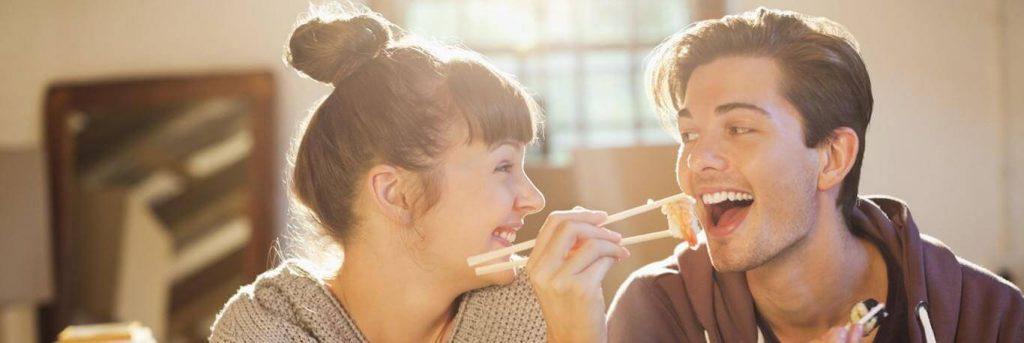 man sits using chopstick eating prawn sushi while girlfriend sitting beside laughing looking