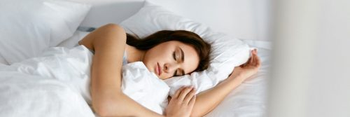 woman sleeping well tightly on bed beside white pillows