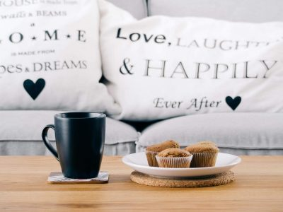cup cake on white plank next to black mug beside white pillows on couch