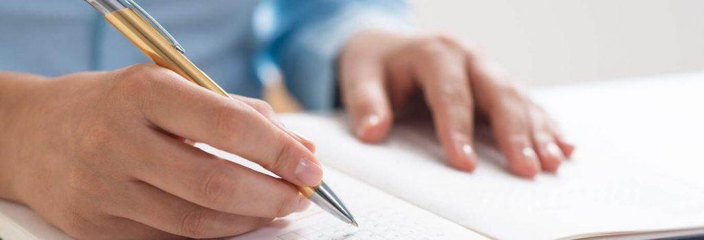 hands holding golden pen writing
