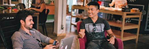 two men sits in busy coffee shop happily talking smiling discussing work