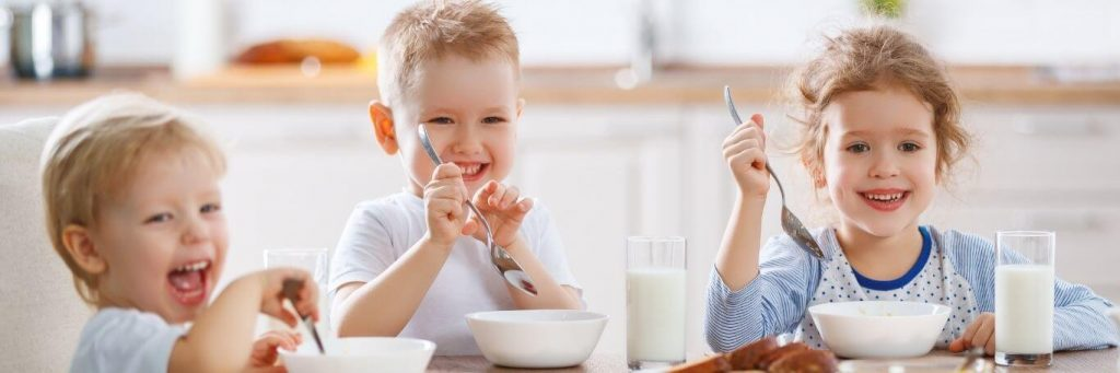 three kids happily sits eating healthy food drinking milk
