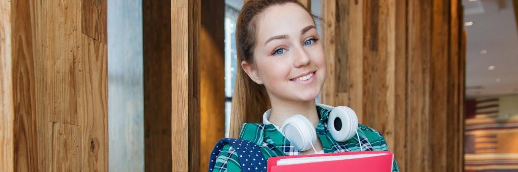 girl teenager wearing headphone stands in library holding red cover document smiling