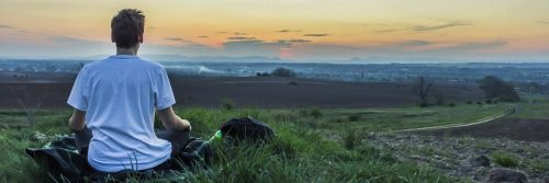man sits on green grass facing backward meditating in sunset dark sky