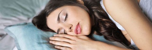 woman lies on blue pillow sleeping nicely