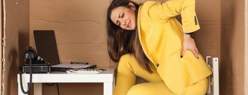 woman wearing yellow suit sits on low chair feeling lower back hurt while working on laptop