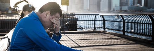 man sits on bench near seaport hand in face feeling sad