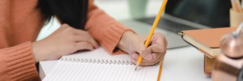 woman hand holding pencil writing on white notebook beside laptop