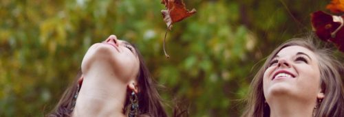two women happily look at beautiful sky red leaves flying