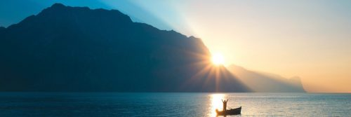 person stands on boat raising hands bloating on blue ocean approaching mountain in blue sunny sky