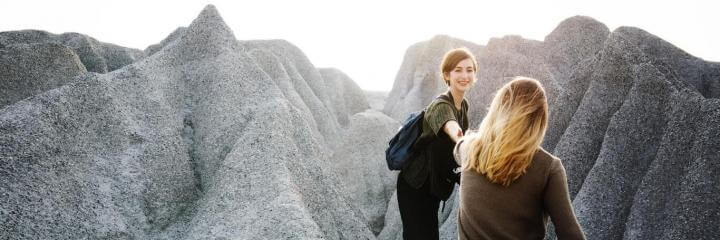 two women climb rocks in shining sky