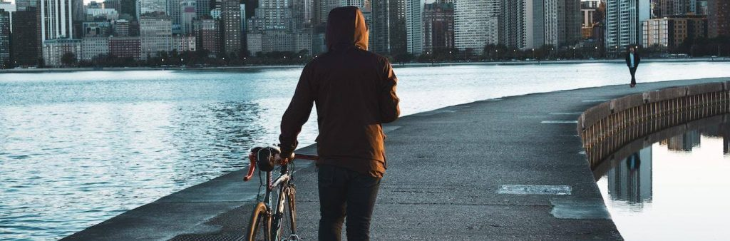man walks his bike along footpath between ocean approaching busy city