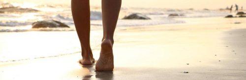 legs walking on sand on beach