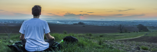 man sits on grass concentrates on meditation breathing in sunset sky