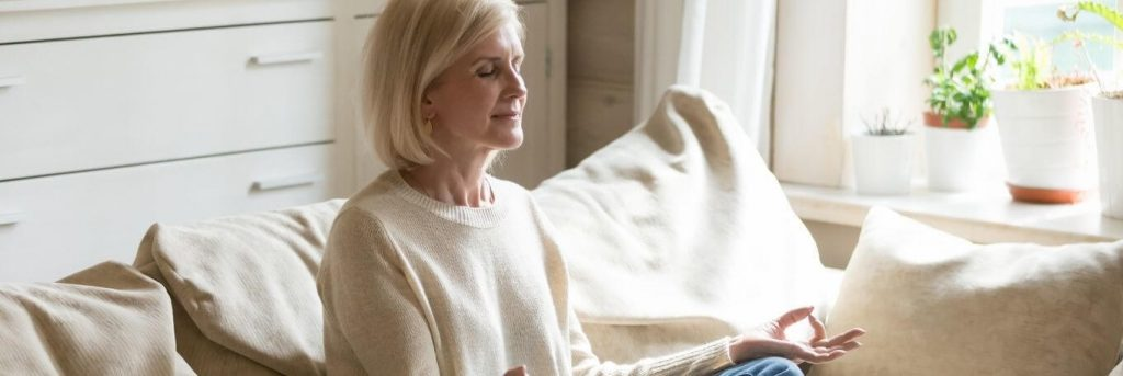 elderly woman sits on couch focuses on meditation breathing in living room