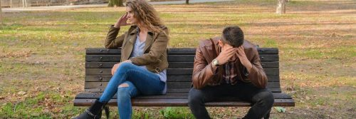 couple sits on bench having conflict while man hands in face upset