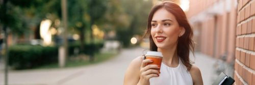 woman stands on street holding coffee cup smiling