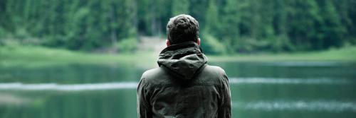 man stands alone facing backward looking at lake mountain