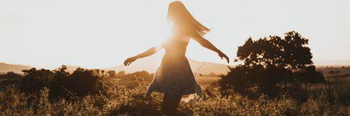 girl happily walking in field feeling grateful in sunny sky