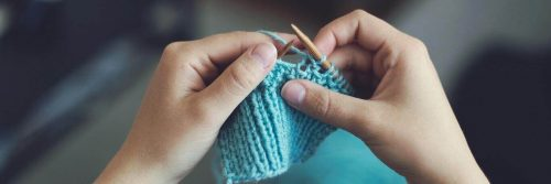 two hands holding needle knitting blue wool