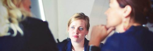 woman looks at two colleges talking in office