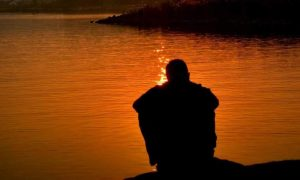 person sits alone beside lake feeling sad in quiet environment