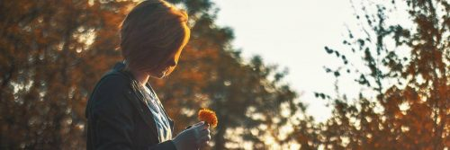 short hair woman holds small orange flower standing in forest in sunny sky