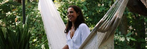 woman sits on white hammock happily smiling in forest