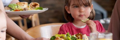 little adorable girl sits beside healthy vegetable dishes eating vegetable cucumber
