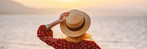 woman stands on beach hand on hat facing backward watching awesome sunset