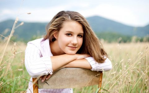 woman sits on chair on field happily smiling posing for photos