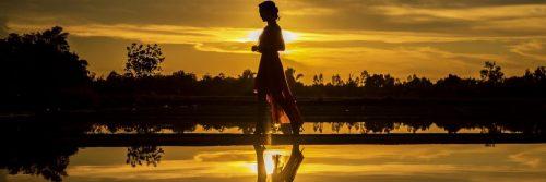 woman walks alone along lake in sunset dark sky