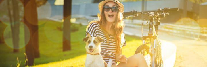 happy woman sits with little pet puppy beside bicycle in park in sunny sky