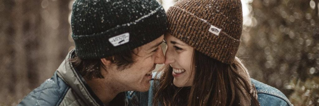 couple wearing winter hat stands smiling in sunny snowy sky