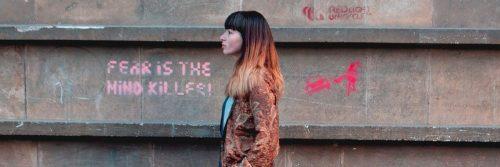 woman walks on street beside wall having pink gravity detailing fear is the mind killer