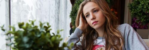 young woman sitting beside window plant pot thinking worrying